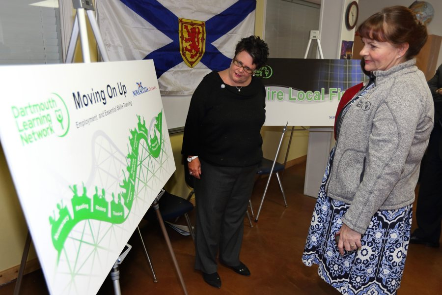 Community Services Minister Joanne Bernard and Lesley Dunn, executive director of the Dartmouth Learning Network, look over a poster for the  Moving on Up: Employment Readiness program.
