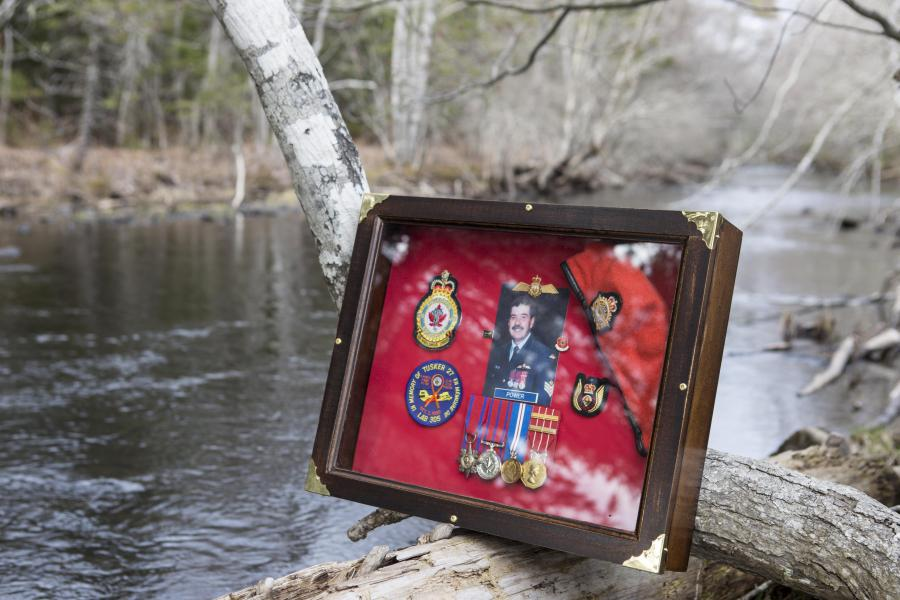 A shadow box including Sgt. Kenneth James Power's photo, beret, and medals placed in front of the brook.