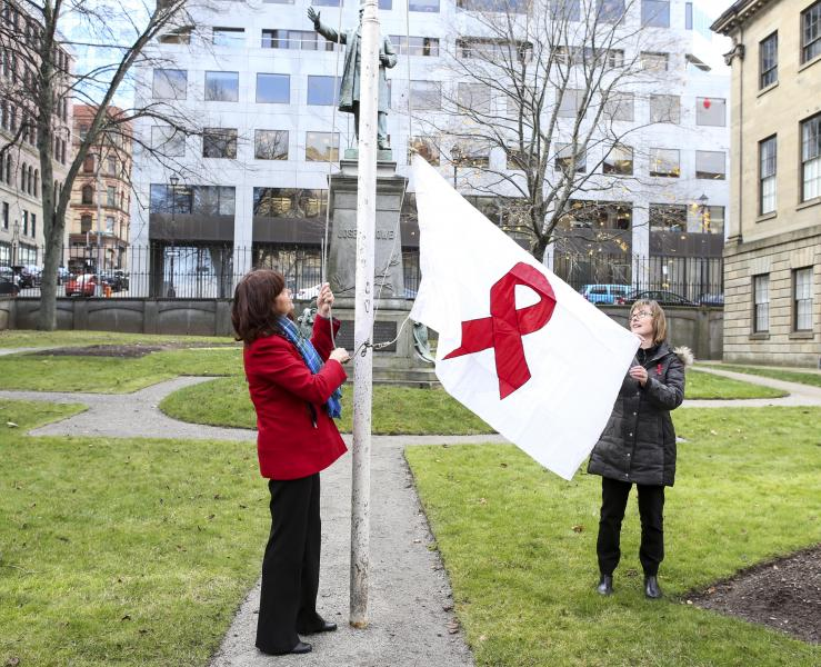 From left: Cole Harbour-Eastern Passage MLA Joyce Treen, on behalf of Health and Wellness Minister Leo Glavine and Michelle Proctor-Simms, director of the Nova Scotia advisory commission on AIDS, raise the flag.