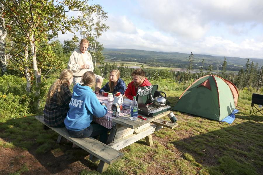 A family sits at a picnic table in front of a tent, on a camp lot overlooking a valley below.