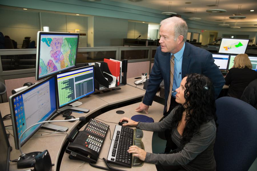 911 call taker Rebecca Mayer demonstrates the computer system for Emergency Management Minister Mark Furey.