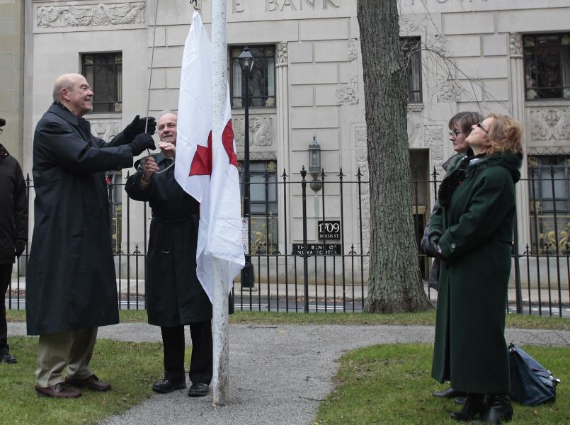 Minister Glavine and Bill Hart of the Nova Scotia Advisory Commission on Aids raise the red ribbon flag to mark HIV-AIDS Awareness Week at Province House.