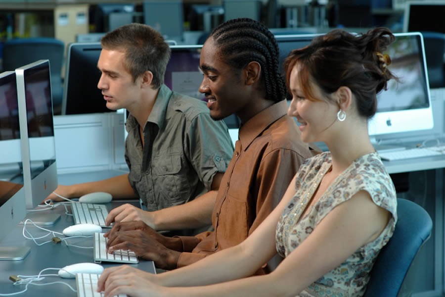 Three young people working at computers