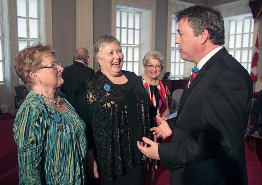 Ordre de la Pléiade medal recipients Marie Stella Doucet, Jocelyne LeBlanc-Tidd and Marie Burkey speaking with Acadian Affairs Minister Michel Samson at Province House