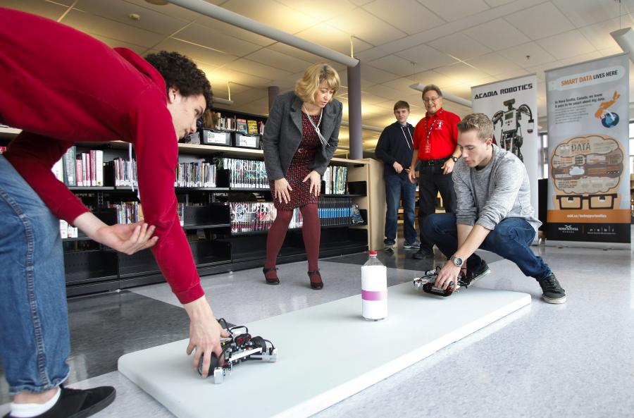 Students from Sir John A. Macdonald High School's robotic team show off their skills for Laurel Broten, CEO and president of NSBI, and Gary Walsh, director, Acadia Robotics.
