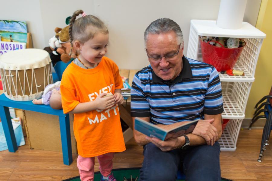 Mi'kmaw linguist Bernie Francis reads to Brielle Pennell at the Mi'kmaq Child Development Centre