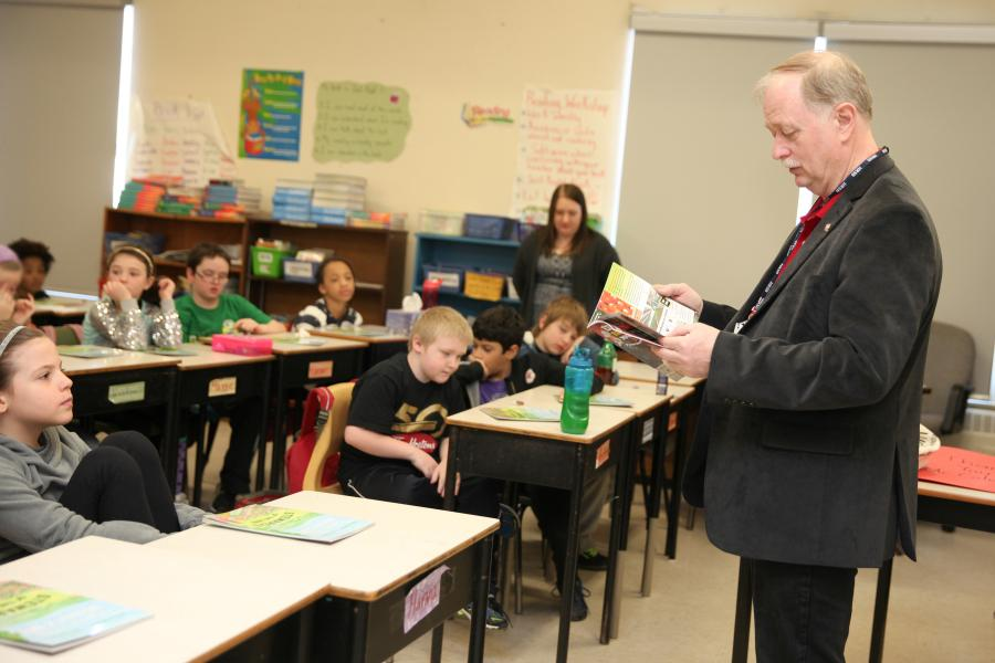 Students listen as Agriculture Minister Keith Colwell reads a book about agriculture