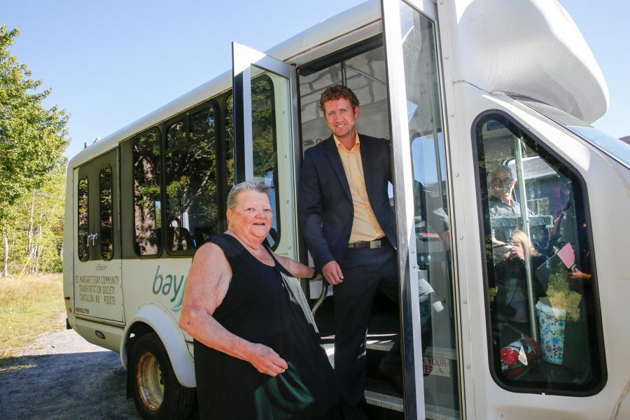 Timberlea-Prospect MLA Iain Rankin helps Ruth Zwicker board the BayRides bus which serves St. Margaret's Bay area. He announced funding for the service on behalf of Municipal Affairs Minister Zach Churchill.