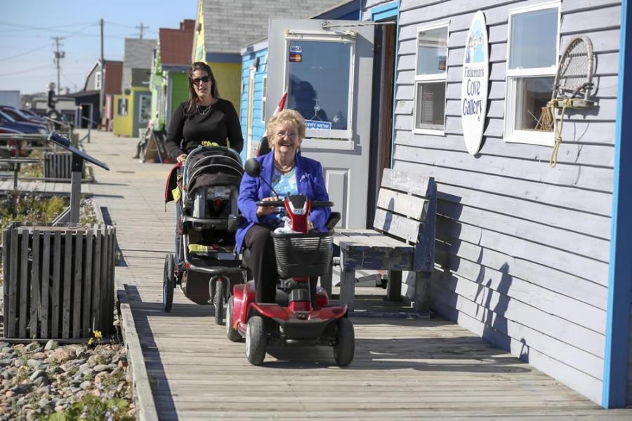 Carol Nickerson, a local volunteer, on the boardwalk at Fisherman's Cove . Paula Canning follows with her son Tom in a stroller.