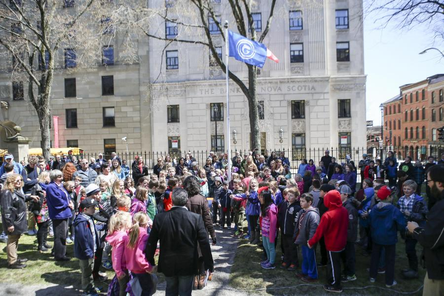 Members of the Gaelic community and students from Waverley Memorial Elementary School help raise the flag of the Gaels at Province House.