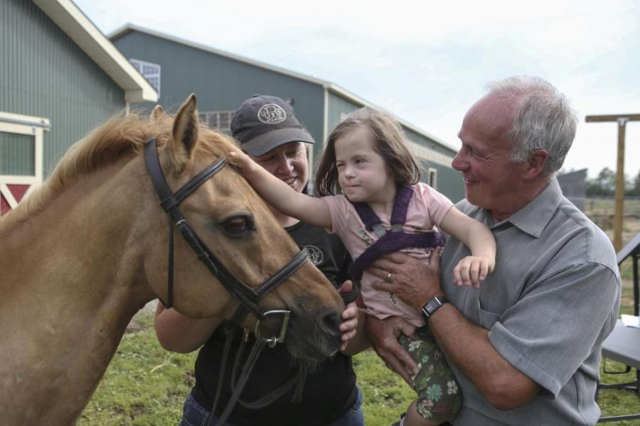 Cathy Meisner and her five-year-old daughter, Emily, visit with Health and Wellness Minister Leo Glavine at the Free Spirit Equestrian Centre in Aylesford where the Minister announced a mental health grant for the centre.