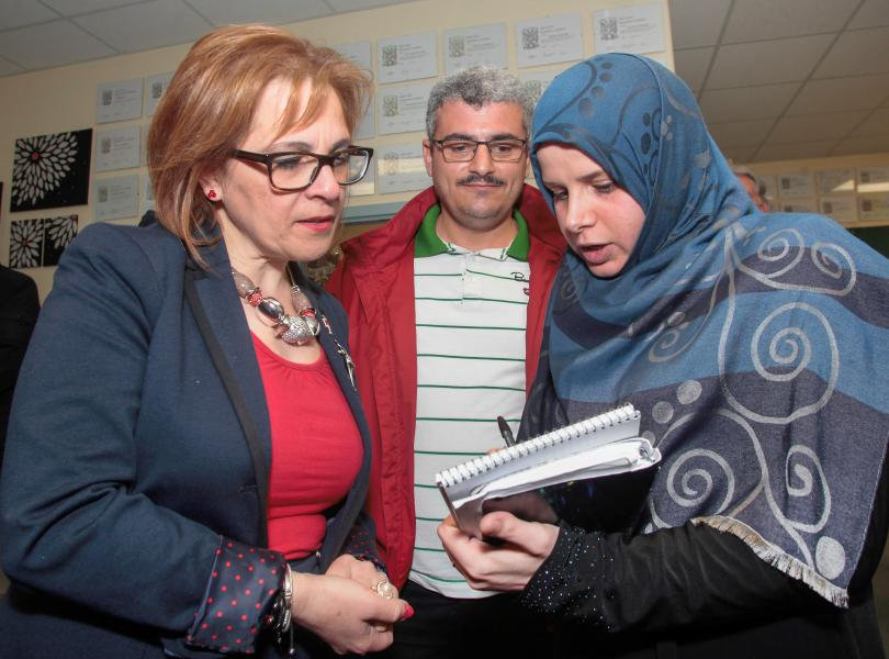 Immigration Minister Lena Metlege Diab, left, helps Syrian refugees Jyab Khatib, centre, and Khayriye Hayane at the office of the Valley Community Learning Association.