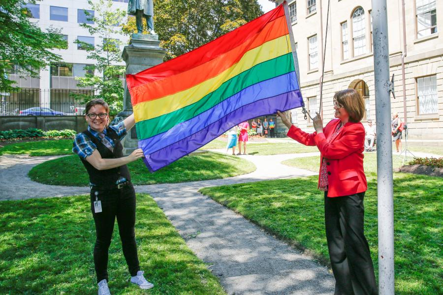 Left: Maddi MacDonald, co-chair of the LGBTI Network, and Deputy Premier Diana Whalen hold the pride flag at Province House.