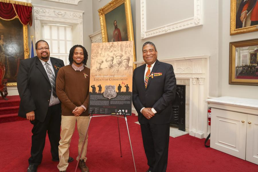 Russell Grosse, Black Cultural Centre (left), and African Nova Scotian Affairs Minister Tony Ince (right) join poster artist Paul Adams, Jr. at the unveiling of the 2016 African Heritage Month poster.