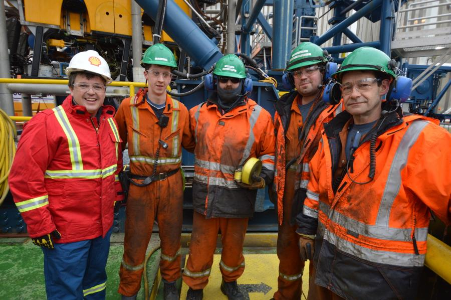 Energy Minister Michel Samson stands with crew members of the Stena IceMAX, Shell Canada's drillship.