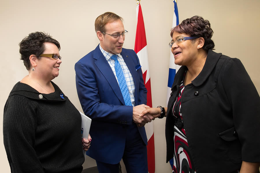 Opal Brinton, member at Needham Housing Co-op, chats with Minister responsible for Housing Nova Scotia Joanne Bernard, while shaking hands with federal Justice Minister Peter MacKay.