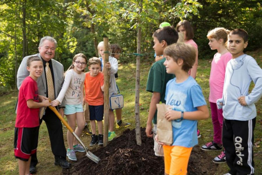 Natural Resources Minister Lloyd Hines plants a tree with elementary school students