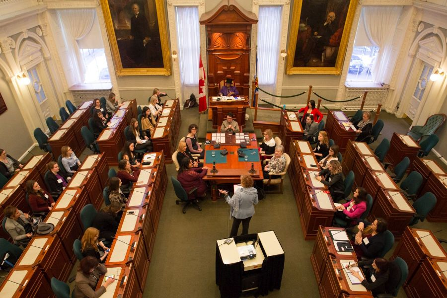 Sue Bookchin (standing), project co-coordinator of Be the Peace, discusses women in leadership with women (ages 18 to 23) from all over Nova Scotia in the legislative chamber of Province house.